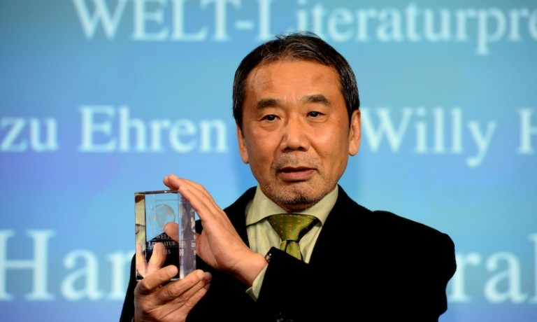 Japanese writer Haruki Murakami poses with his trophy prior to an award ceremony for the Germany's Welt Literature Prize bestowed by the German daily Die Welt, in Berlin on November 7, 2014.  AFP PHOTO / JOHN MACDOUGALL