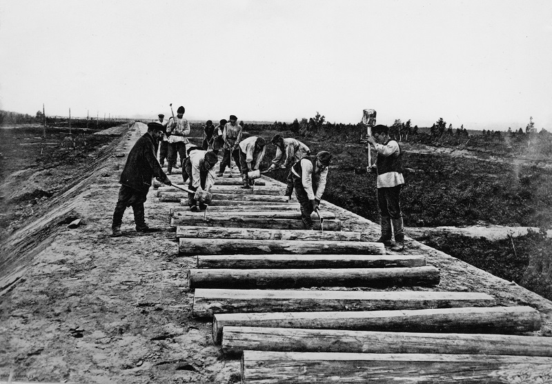 A team of workmen building part of the Trans-Siberian Railway in Russia. They appear to be splitting large logs, probably for the laying of sleepers. Construction took place between 1891 and 1913, and cost 1.455 billion roubles. The railway, which is the longest in the world at over 9000 kilometres, links Moscow with the Pacific port of Vladivostok. Date: 1891-1913