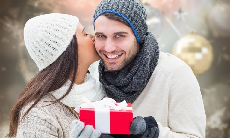 33962819 - winter couple holding gift against blurred christmas background
