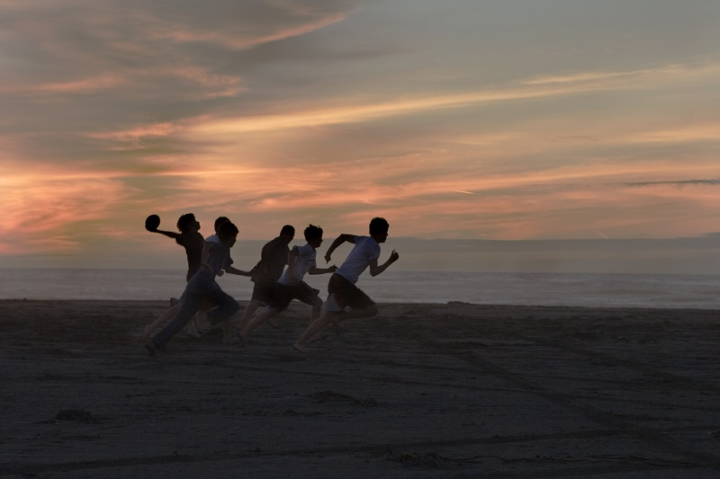 Teenagers playing ball on beach